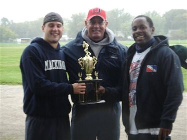 Coach Bob Newvine (center) presents the Most Valuable Player trophy to winners Jack